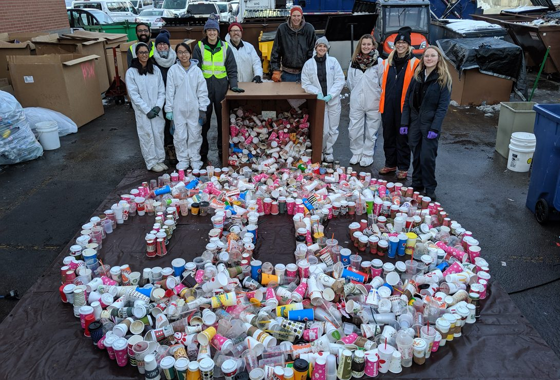Volunteers stand around a UIC logo made from discarded disposable beverage containers.